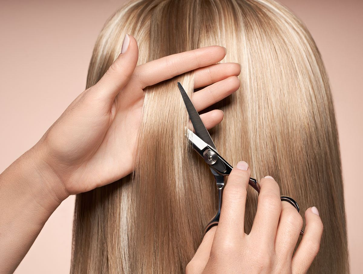 scissors cutting blonde hair